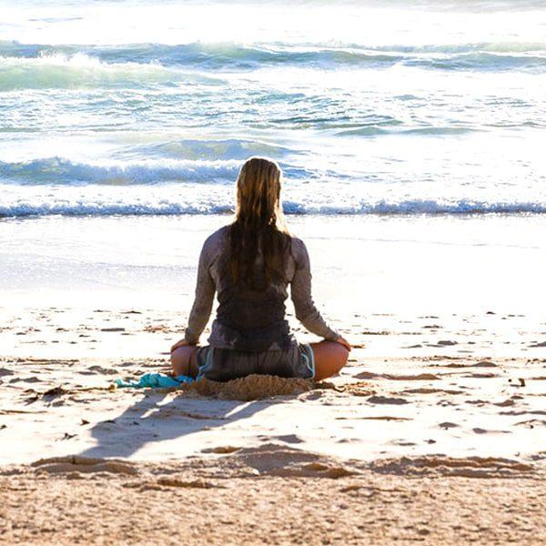 woman meditation next to ocean during meditation retreat in california